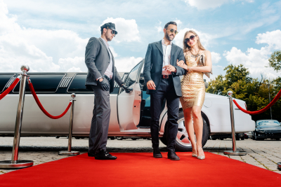 couple arriving with limousine walking in red carpet