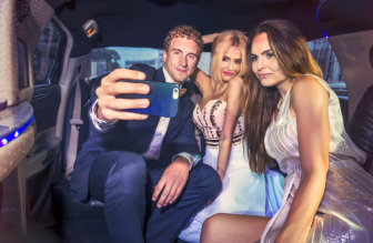 adults taking picture inside limousine