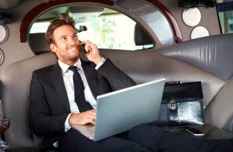 male in tuxedo with laptop smiling while talking through his phone