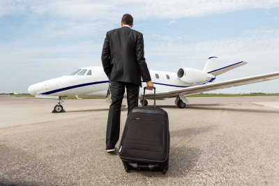 businessman with luggage walking towards corporate jet